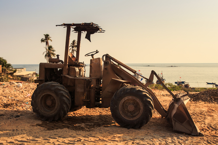 closeup of small tractor with scoop stands on coast building ground against palms sea and blue sky Stock Photo