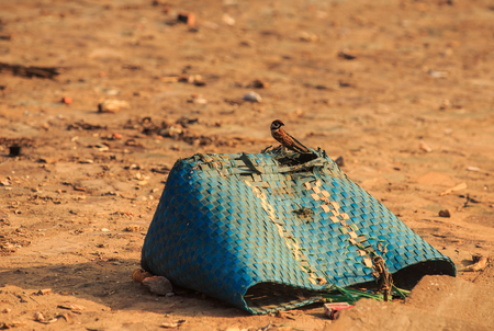 closeup blue dirty lost broken torn plastic wicker bag on ground makes shade at bright sunlight
