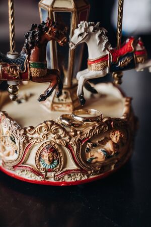 wedding rings lie on a toy carousel with little horses Foto de archivo