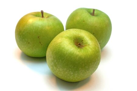 Green ripe granny apples on a white background