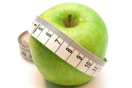 Green apple wrapped by measuring tape isolated on white background