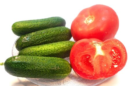 Cucumbers with tomatoes in a plate on a white background
