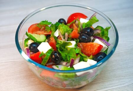 Greek salad with tomatoes, cucumbers and feta cheese with olives on the table.