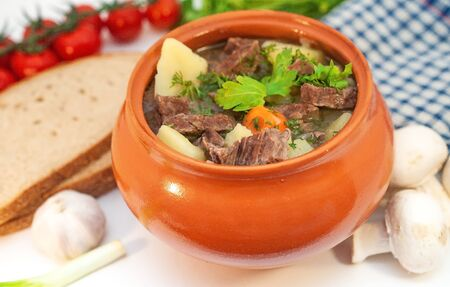 Roast in a pot with beef meat and potatoes on the table