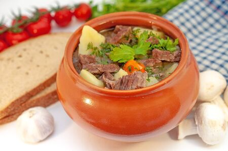 Roast in a pot with beef meat and potatoes on the table.