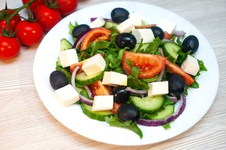 Greek salad with tomatoes, cucumbers and feta cheese with olives on the table Standard-Bild