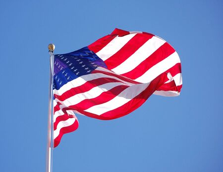 American flag waiving in the wind with blue sky photo