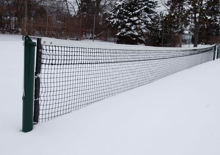 white winter: Tennis court in the snow with trees in background Stock Photo