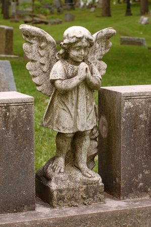 Angel with wings between two headstones in cemetery