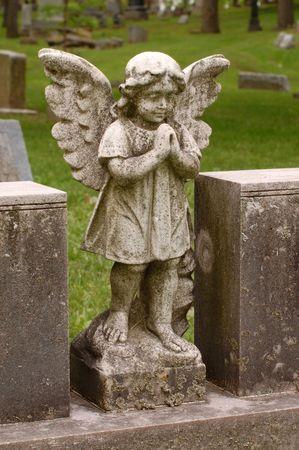 angel cemetery: Angel with wings between two headstones in cemetery