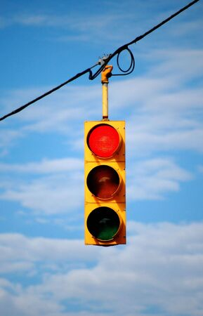 suspended: Suspended stoplight showing red with sky background Stock Photo