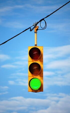 Suspended stoplight showing green, with sky background photo