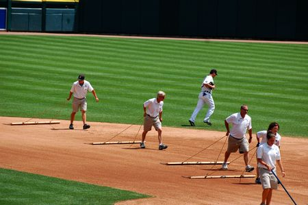groundskeeper: DETROIT, MI - JULY 11: Groundskeepers at work during the Detroit Tigers game against the Minnesota Twins on July 11, 2010 in Detroit, Michigan.