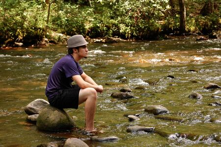 Teenager sitting on river rocks, with hat on, side view photo