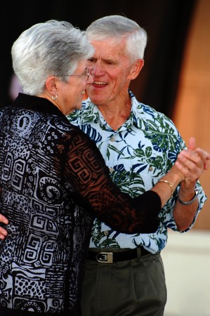 senior couple dancing, holding hands and smiling