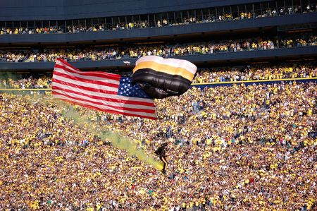 michigan state: ANN ARBOR, MI - OCTOBER 09: 101st Airborne Division Parachute Demonstration Team member parachutes past the crowd at Michigan Stadium before the Michigan vs. Michigan State football game October 9, 2010.