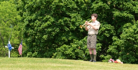 ANN ARBOR, MI - MAY 27: Boy scout playing taps at the annual Memorial Day observance on May 27, 2012 at Arborcrest Memorial Park in Ann Arbor, MI
