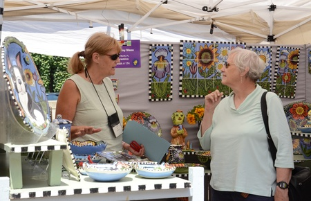 ANN ARBOR, MI - JULY 20: Toni Mann, a ceramics artist from Lake Worth, Florida, speaks to a customer at the Ann Arbor's South University Art Fair, one of four art fairs taking place in Ann Arbor July 18-21, 2012.