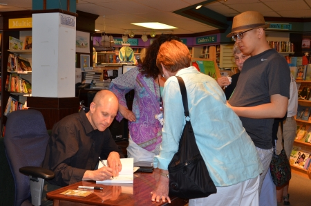 ANN ARBOR, MI - JUNE 25: New York Times bestselling author Jim Ottaviani autographs a book  at a book signing for his new book Primates at Nicola