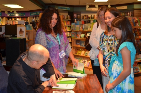 book: ANN ARBOR, MI - JUNE 25: New York Times bestselling author Jim Ottaviani autographs a book  at a book signing for his new book Primates at Nicola