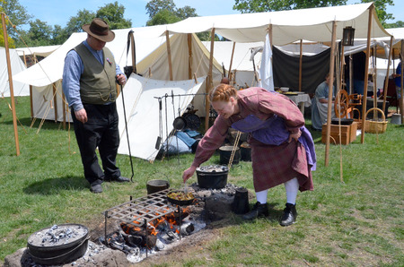 reenactor: DEARBORN, MI - MAY 26: Civil-war era re-enactor cooking during the Civil War remembrance at Greenfield Village May 26, 2013.  Editorial