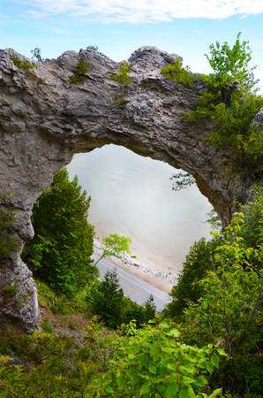 mackinac: MACKINAC ISLAND, MI, USA- JUNE 21: Arch Rock in Mackinac Island, MI, shown here on June 21, 2014, is fifty feet wide and was formed by erosion of the soft rock underneath the breccia rock that remains. Editorial
