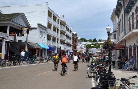 mackinac: MACKINAC ISLAND, MI, USA- JUNE 21: Bicyclist ride in downtown Mackinac Island, MI on June 21, 2014. No powered automobiles are allowed on the island.