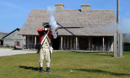 reenactor: Mackinaw City, MI, EE.UU.-22 de junio: Un re-enactor demuestra c�mo disparar un mosquete en el Fuerte Michilimackinac en Mackinaw City, MI, el 22 de junio de 2014. Editorial