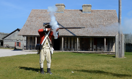 reenactor: MACKINAW CITY, MI, USA- JUNE 22: A re-enactor demonstrates how to fire a musket at Fort Michilimackinac in Mackinaw City, MI on June 22, 2014.  Editorial