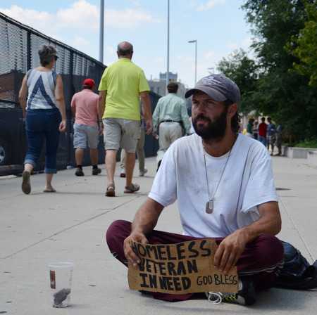 DETROIT, MI - JULY 6: Homeless veteran waits as people walk past him as he begs for money in Detroit, MI on July 6, 2014 Editorial