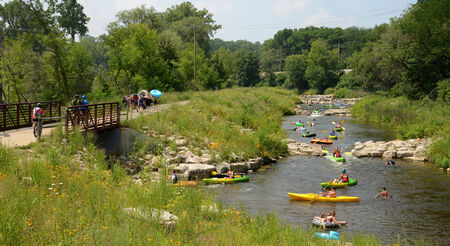 ANN ARBOR, MI - AUGUST 3: Kayakers enjoythe rapids at the Argo Cascades in Ann Arbor, MI on August 3, 2014 while others walk back to the start.   新聞圖片
