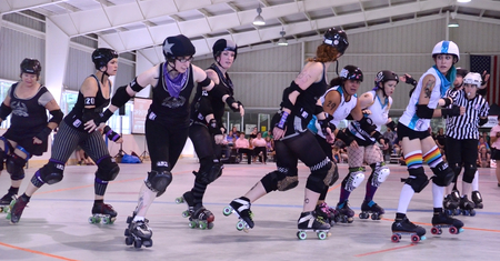 bout: ANN ARBOR, MI - AUGUST 2: Arbor Bruising Co. jammer skates around the pack in their bout against  Raggidy G-Rap Attack! in Ann Arbor, MI on August 2, 2014. Editorial