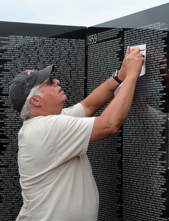 exhibit: HAMBURG, MI - AUGUST 30: Volunteer gets a rubbing of a name from the traveling Moving Wall Vietnam War memorial exhibit in Hamburg, MI on August 30, 2014.