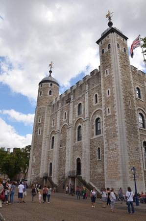 beefeater: LONDON - AUGUST 6: Tourists walk past the White Tower at the Tower of London on August 6, 2015.