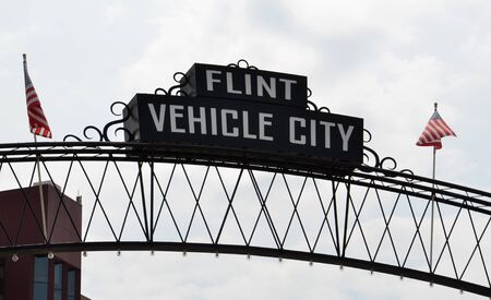 flint: FLINT, MI - AUGUST 22: Flint Vehicle City sign, shown here on August 22, 2015, spans downtown Flint, MI. Editorial