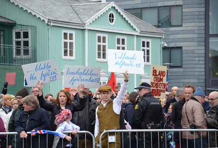 protesters: REYKJAVIK, ICELAND - JUN 17:  Protesters hold up signs on independence day in Reykjavik Iceland on June 17, 2015.