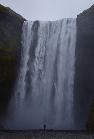 skogafoss waterfall: NEAR SKOGAR, ICELAND - JUN 15:  A person stands before Skogafoss waterfall on June 15, 2015. The fall was in the film The Secret Life of Walter Mitty in 2013.