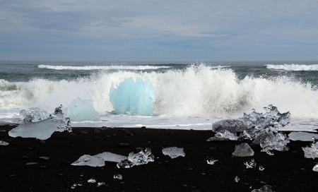 calved: Ocean waves hit icebergs on the shore near lake Jokulsarlon, Iceland on June 18, 2015. The icebergs calved from the nearby Vatnajokull glacier.