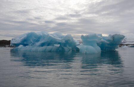 calved: Icebergs reflect on Jokulsarlon, Iceland on June 18, 2015. The icebergs calved from the nearby Vatnajokull glacier.