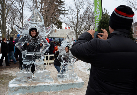 plymouth: PLYMOUTH, MI - JANUARY 11:  A man photographing two people at the Plymouth Ice Festival on  January 11, 2015. Editorial