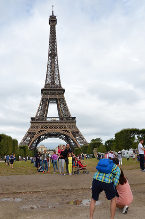 PARIS - AUG 8:  Tourists taking photographs at the Eiffel Tower in Paris, France on August 8, 2016. It was originally the entrance to the 1889 World Fair.