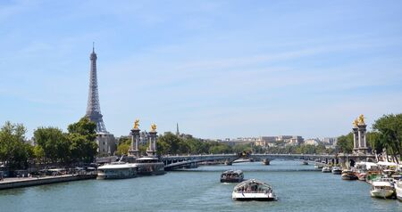 PARIS - AUG 8:  View of the Eiffel Tower from a bridge over the Seine in Paris, France is shown on August 8, 2016. It was originally the entrance to the 1889 World Fair.