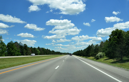 Highway with cars in distance, sunny skies with a few puffy clouds