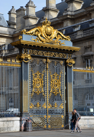 PARIS - AUG 7:  A couple walks past the gate of the Palais de Justice in Paris, France on August 7, 2016. In the past it served as the residence of some of the kings of France.