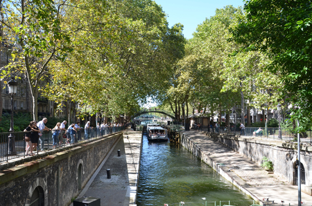 PARIS - AUG 7:  Tourists are shown on a boat ride in the Canal Saint-Martin in Paris, France on August 7, 2016.  It was ordered by Napoleon in 1802 to bring fresh water to Paris. Editorial