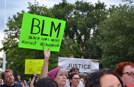 ANN ARBOR, MI - AUG 13: A woman holds up a sign at a rally in solidarity with the counter-protesters of Charlottesville in Ann Arbor, MI on August 13, 2017. Sajtókép