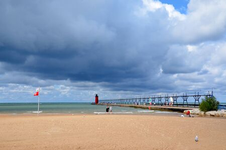 SOUTH HAVEN, MI  USA - AUGUST 12, 2017: Visitors watch the stormy clouds at a quiet South Haven beach on Lake Michigan, with the lighthouse in the background. Sajtókép