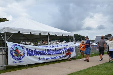 SOUTH HAVEN, MI  USA - AUGUST 12, 2017: Visitors stroll past a National Blueberry Festival sign at the  South Haven riverfront. Sajtókép