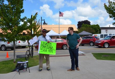 SOUTH HAVEN, MI  USA - AUGUST 12, 2017: An activist encourages visitors to the National Blueberry Festival in downtown South Haven to sign a petition to legalize marijuana in Michigan.