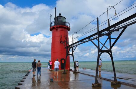 SOUTH HAVEN, MI  USA - AUGUST 12, 2017: Visitors admire the South Haven lighthouse, at South Haven beach on Lake Michigan.